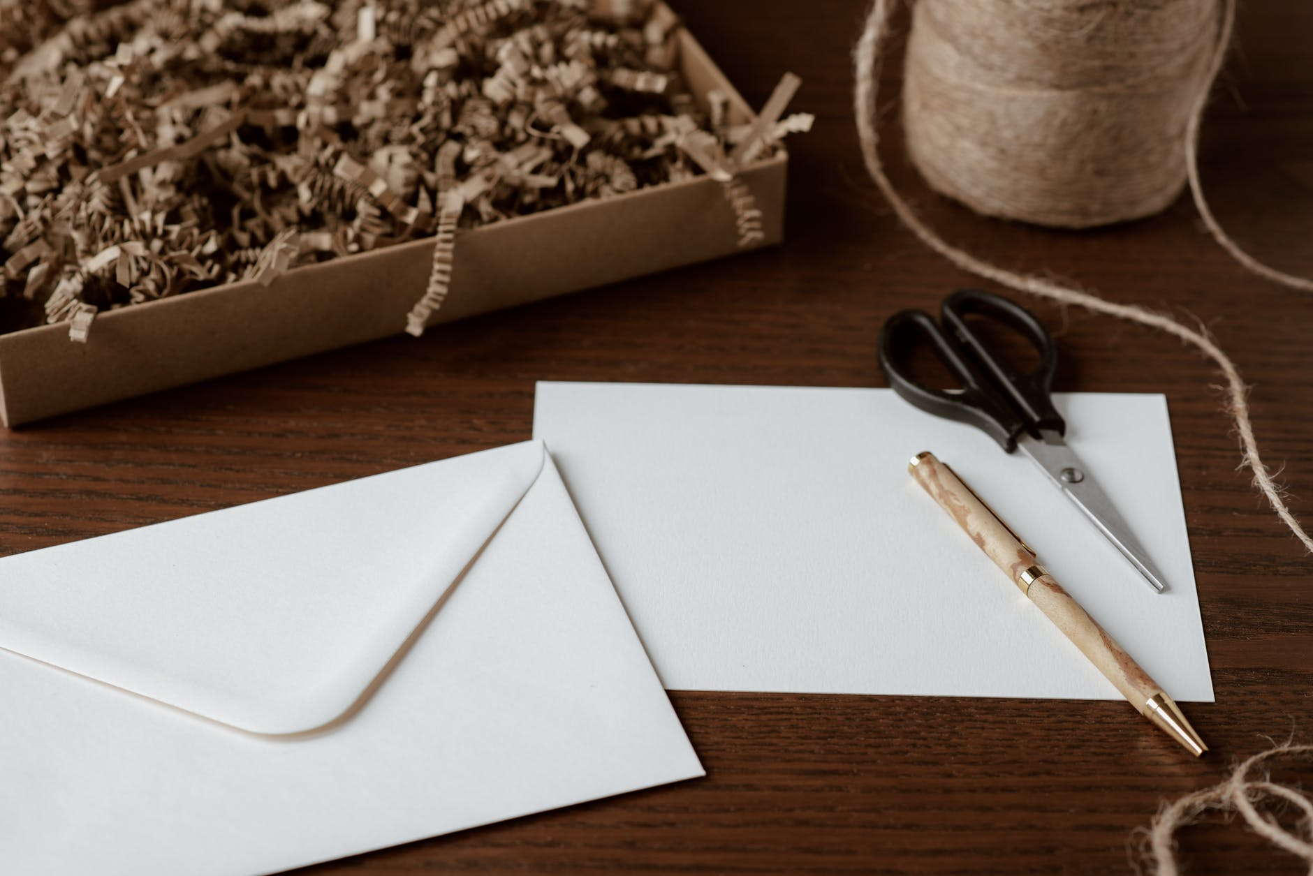 envelope and pen placed on table near tying twine