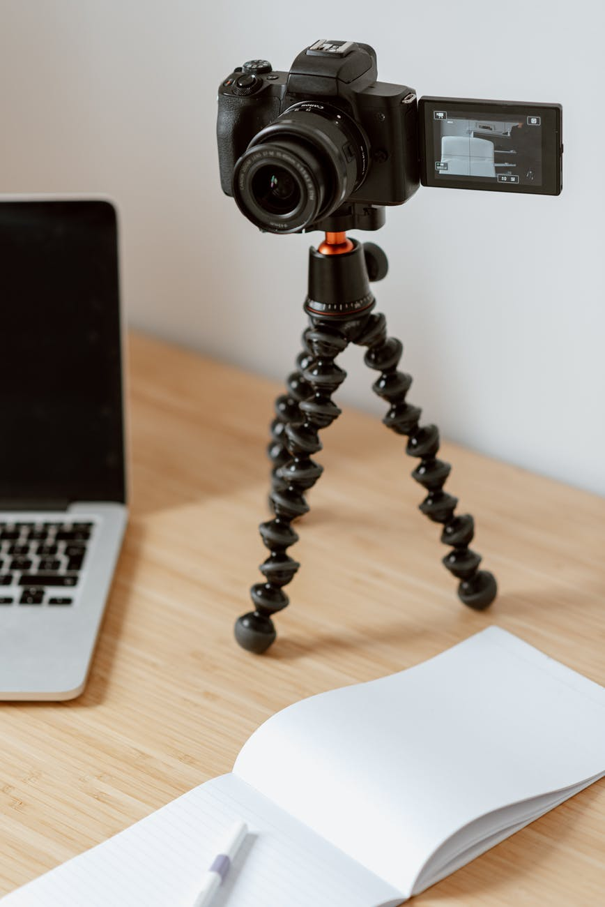 camera on tripod recording video on table