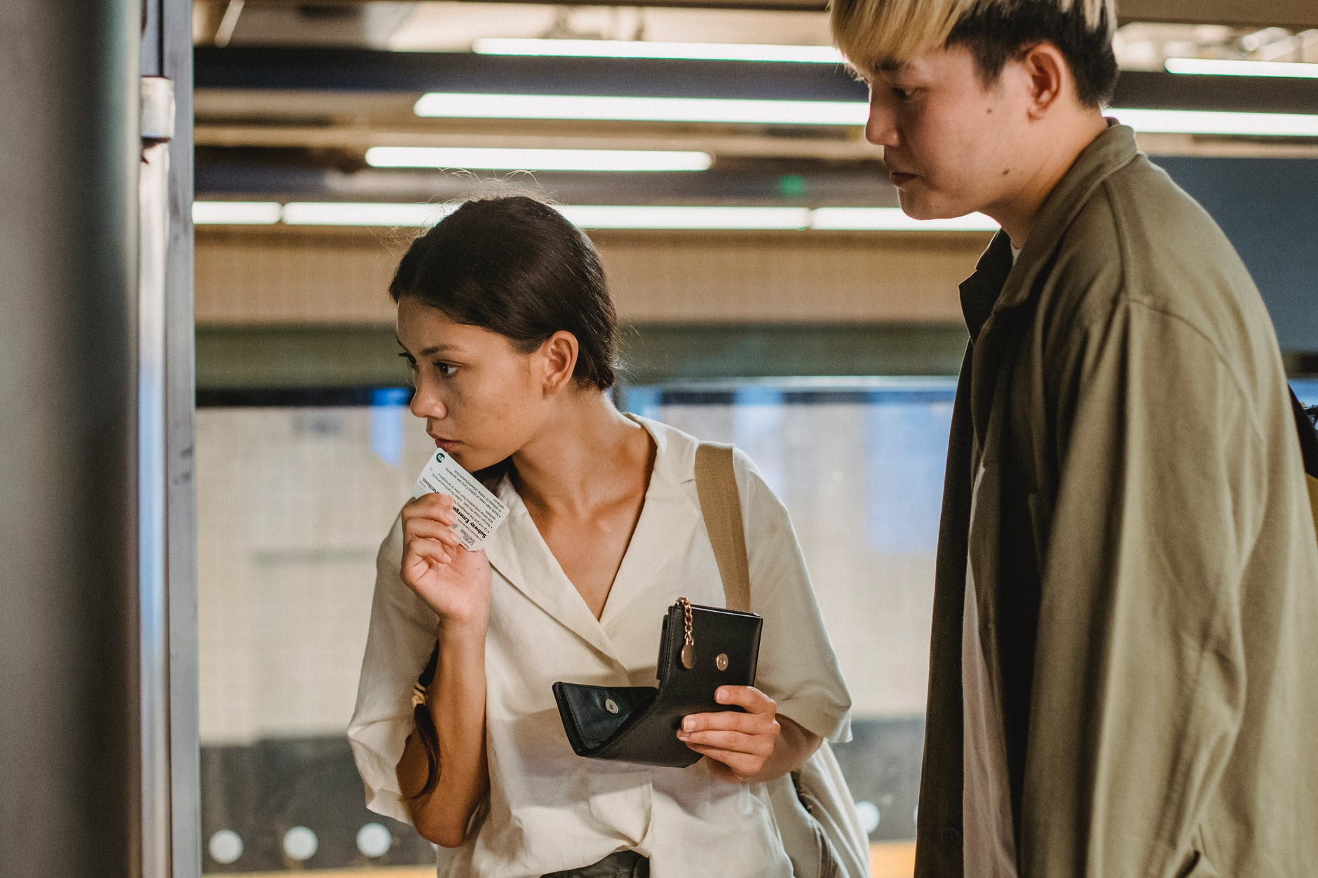 focused asian couple buying ticket on station