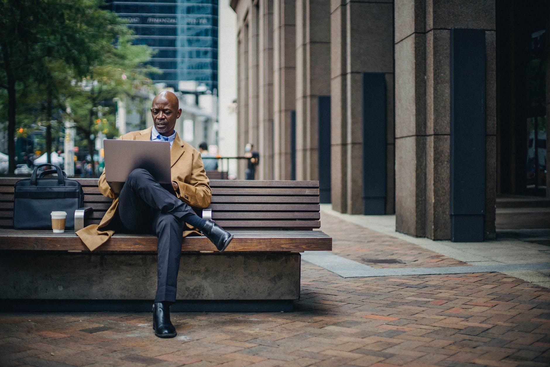 serious black businessman using laptop on city street on bench