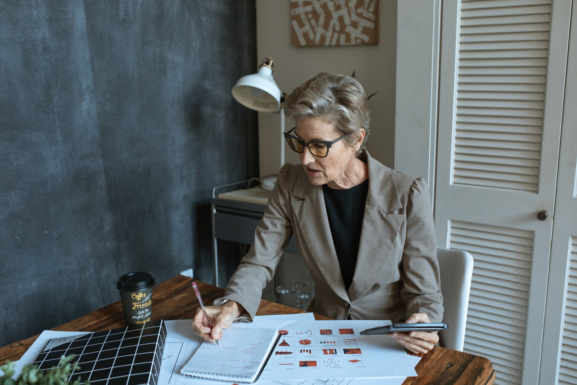 focused businesswoman writing in notebook during work in office
