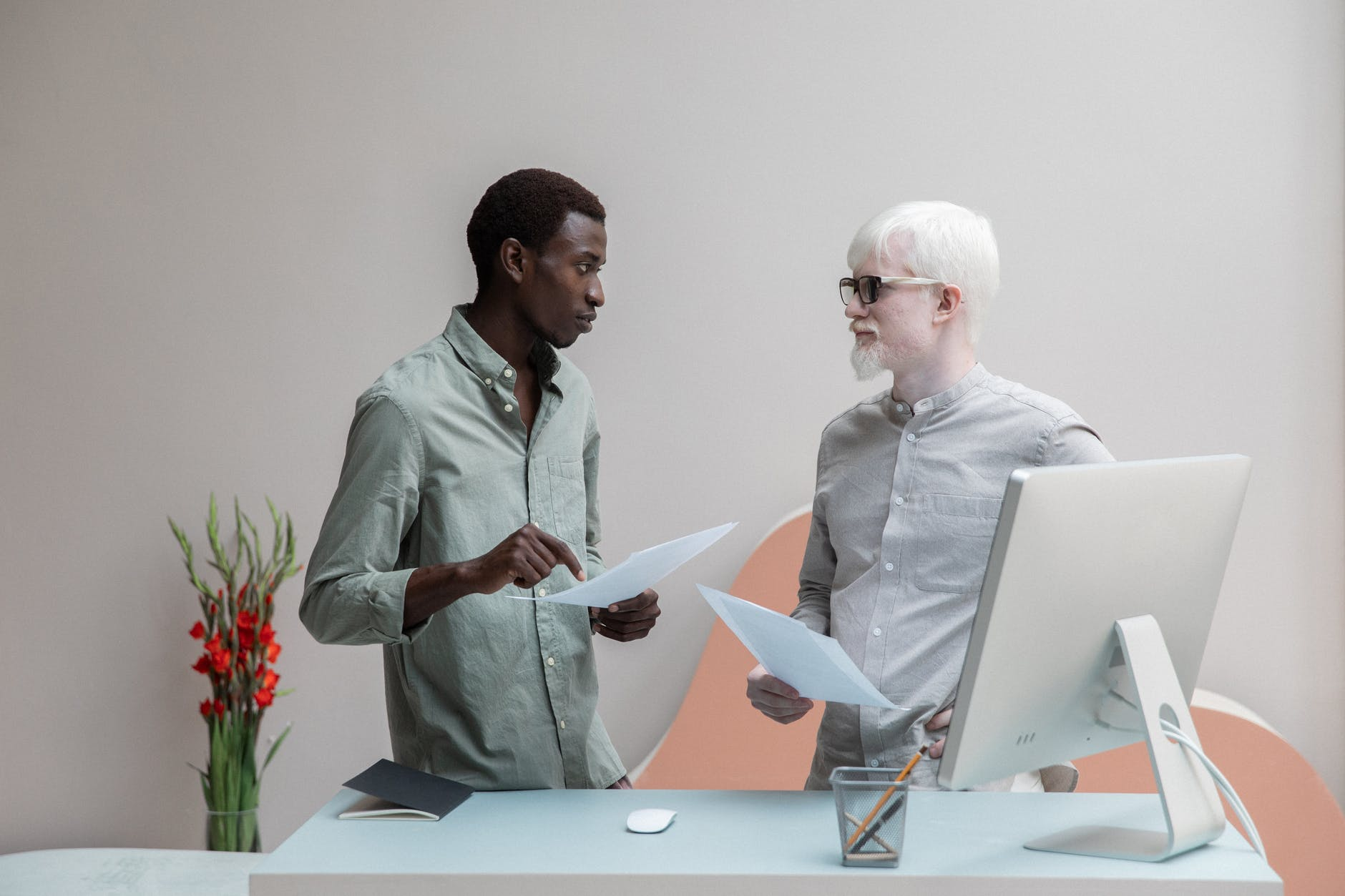 multiracial coworkers with papers in office