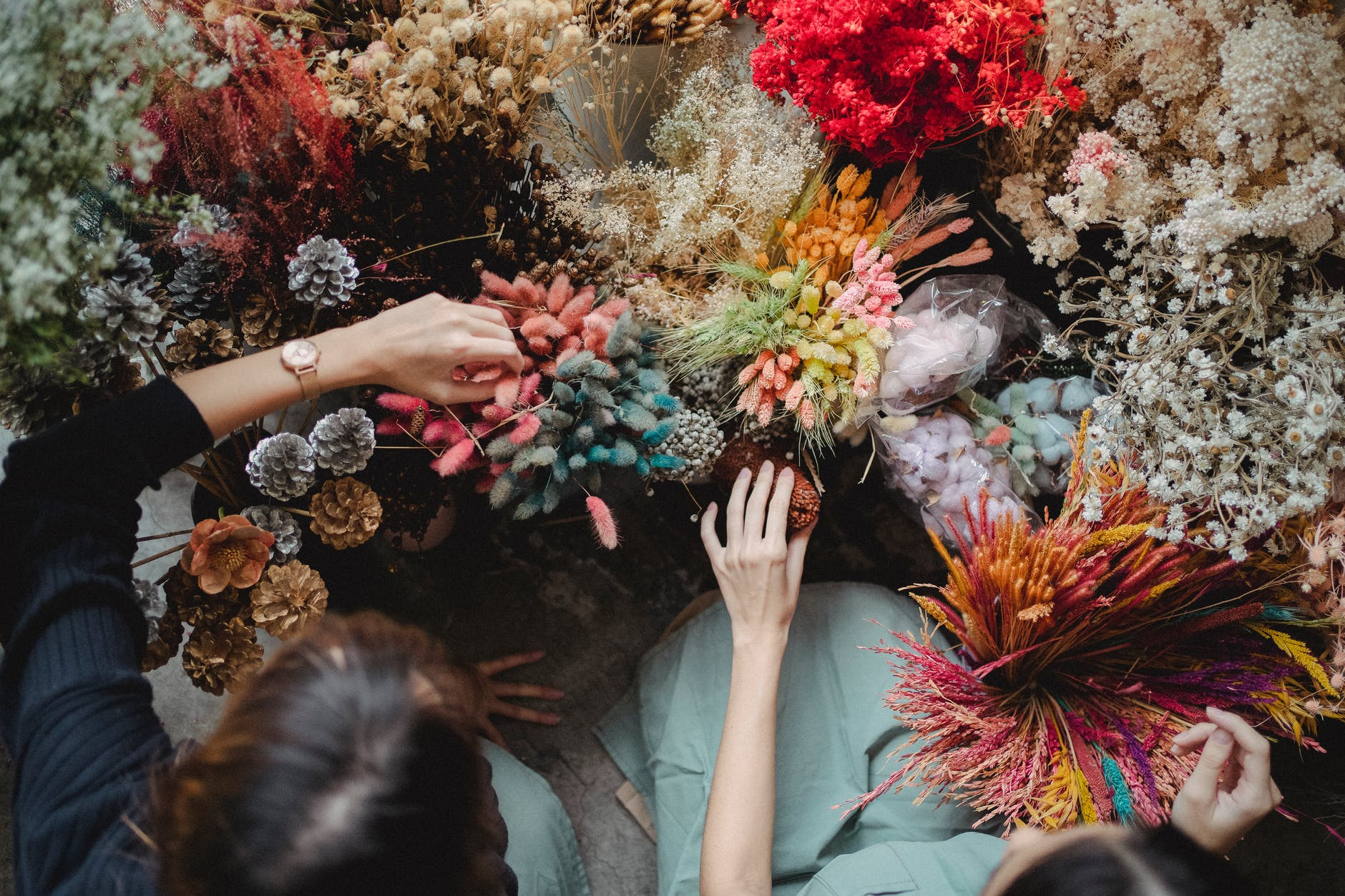 crop faceless florists touching decorative bouquet elements and flowers