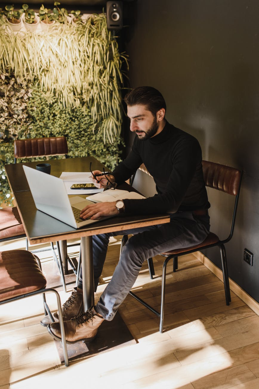 focused man working on laptop in creative workspace
