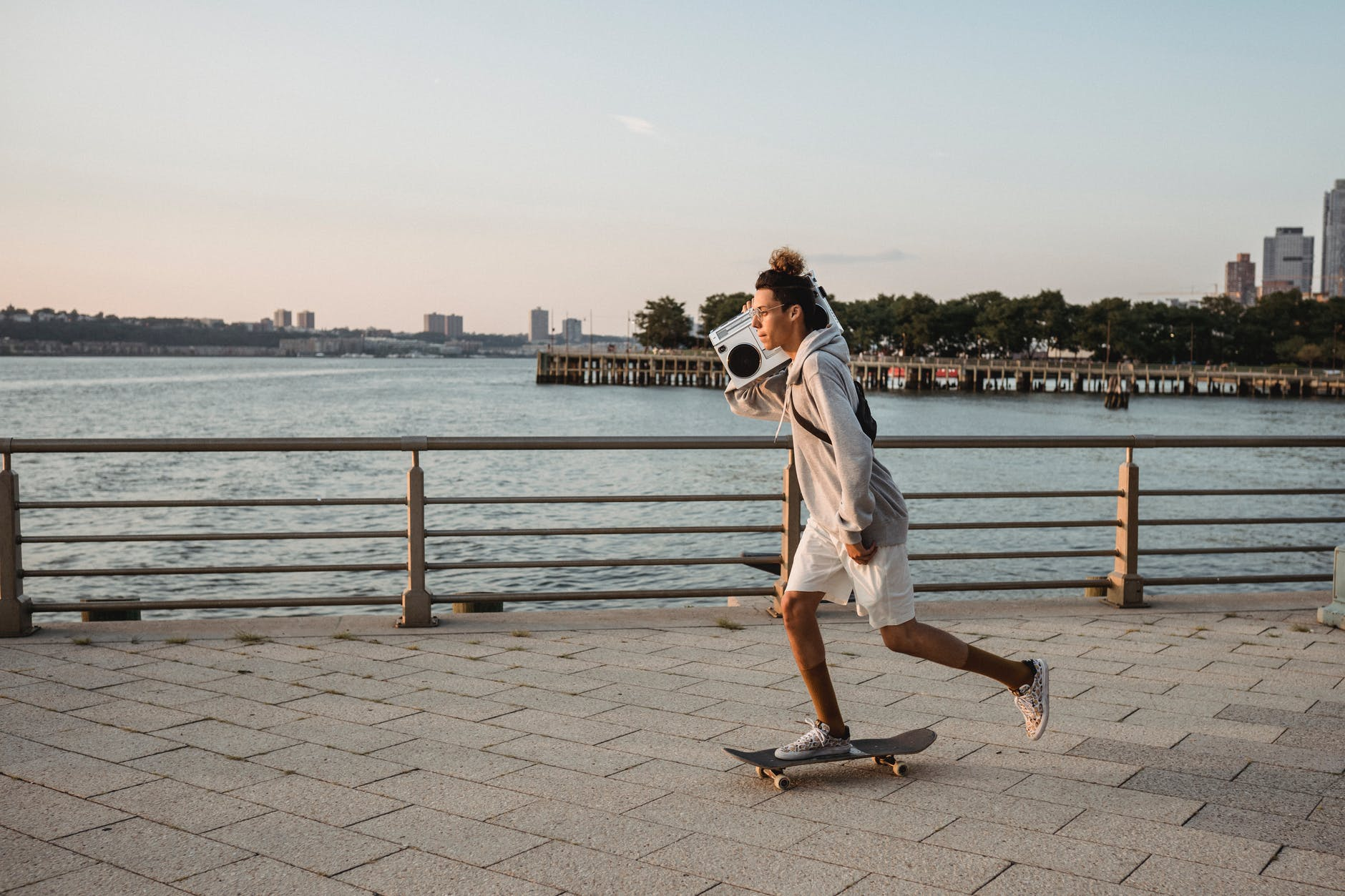 skilled male skater riding skateboard with boombox on embankment